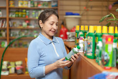 Mature woman chooses agricultural chemistry Royalty Free Stock Photography