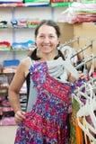 Mature woman  chooses dress Stock Images
