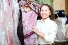Mature woman chooses evening dress Stock Photo