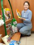 Mature woman chooses fertilization. At garden shop royalty free stock image