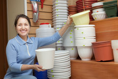 Mature woman chooses a flower pot. In the store for gardeners royalty free stock image