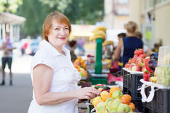 Mature woman chooses fruits Royalty Free Stock Image