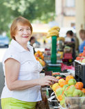 Mature woman  chooses fruits Stock Images
