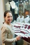 Mature woman   chooses jewelry Stock Photo