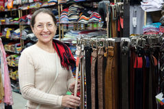 Mature woman  chooses  leather belt Royalty Free Stock Images