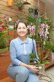 Mature woman chooses  orchid Stock Images