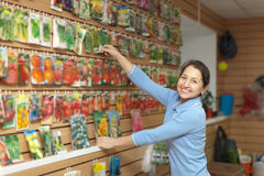 Mature woman chooses packaged seeds Stock Photography