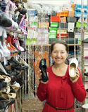 Mature woman chooses shoes Royalty Free Stock Image