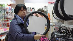 Mature woman in chooses a soft trim for the steering wheel of a car. A mature woman in a blue jacket chooses a soft pad on the steering wheel of a car in the