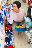 Mature woman choosing cleaning brush in household department Stock Image