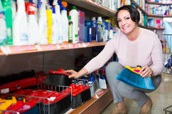 Mature woman choosing cleaning brush in household department Royalty Free Stock Photos