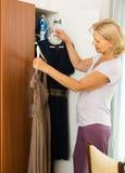 Mature woman choosing dress at home Stock Photography