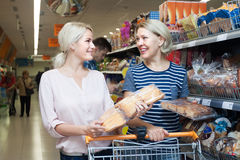 Mature woman choosing pastry in bakery section of supermarket Stock Photos