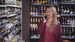Mature woman choosing quality alcohol and talking on cellular in. Beautiful and attractive adult woman with smiling face in casual checkered wear choosing items stock footage
