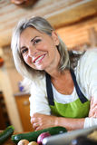 Mature woman choosing vegetable for cooking Royalty Free Stock Image