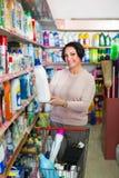 Mature woman choosing washing detergent Royalty Free Stock Image