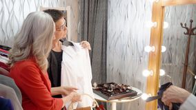 Mature woman choosing white blouse front mirror in showroom. Fashion stylist helping adult businesswoman trying white. Shirt in clothing store. Shopping concept stock footage