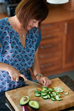 Mature woman chopping vegetables Stock Images