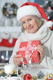 Mature woman with Christmas gift. Beautiful mature woman with Christmas gift on blurred background Royalty Free Stock Images