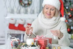 Mature woman with Christmas gift. Beautiful mature woman with Christmas gift on blurred background Stock Photography