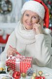 Mature woman with Christmas gift. Beautiful mature woman with Christmas gift on blurred background Stock Images