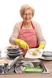Mature woman cleaning the dishes with a brush Stock Images