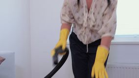 Mature woman cleaning sofa at home stock footage