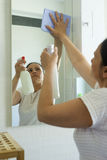 Mature woman with cleaning spray and cloth in bathroom Stock Photo