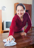 Mature woman cleaning  table with rag Stock Photography