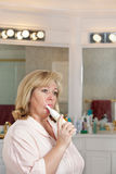 Mature woman cleaning teeth Royalty Free Stock Photo