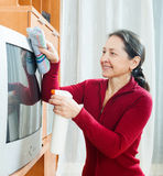 Mature woman cleaning TV Royalty Free Stock Images