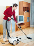 Mature woman cleaning with vacuum cleaner Stock Photo