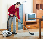 Mature woman cleaning with vacuum cleaner Royalty Free Stock Image