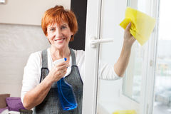 Mature woman cleaning window Stock Image