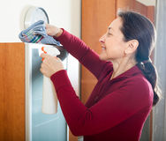 Mature woman cleaning wooden furniture Stock Image