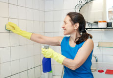 Mature woman cleans tiled wall Royalty Free Stock Photography