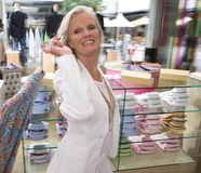 Mature woman in clothing store, holding shirt, smiling, portrait Royalty Free Stock Images