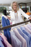 Mature woman in clothing store, holding up shirt, smiling, portrait Royalty Free Stock Photography