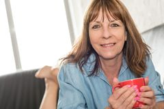 Mature woman during coffee break at home. Smiling mature woman during coffee break at home Stock Photography