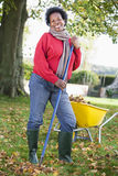 Mature woman collecting leaves in garden Royalty Free Stock Photos