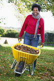 Mature woman collecting leaves in garden Stock Image