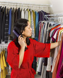 Mature woman combing hair while in closet Stock Photography