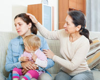 Mature woman comforting adult daughter with baby Royalty Free Stock Photo
