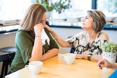 Mature woman comforting her friend after breakup. Young hispanic women feeling upset and crying after a bad breakup while her friend comforts her at cafe royalty free stock images