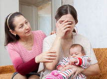 Mature woman comforts crying daughter with baby. Mature women comforts crying adult daughter with baby at home Royalty Free Stock Image