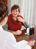Mature woman complaining to  doctor about feels Royalty Free Stock Images