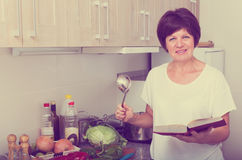 Mature woman cook book Stock Image