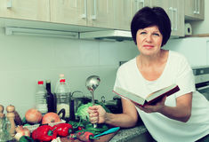 Mature woman cook book Stock Photo