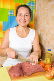 Mature woman is cooking beef Royalty Free Stock Image
