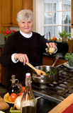 Mature woman cooking healthy food. Stock Photos
